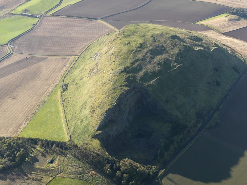 Oblique aerial view of the remains of Traprain Law fort, taken from the ENE.