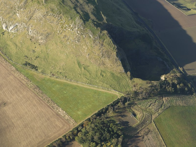 Oblique aerial view of the remains of terraces on the flank of Traprain Law fort, taken from the ESE.