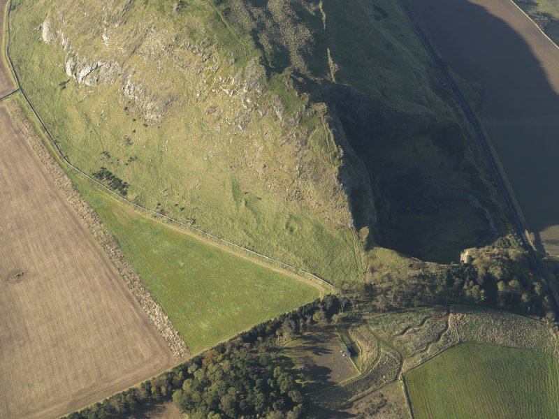 Oblique aerial view of the remains of terraces on the flank of Traprain Law fort, taken from the E.