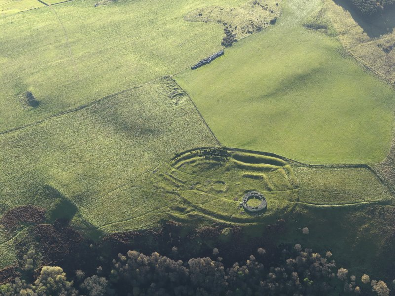 Oblique aerial view of the remains of the fort, settlement and broch at Edin's Hall and the adjacent settlement, taken from the NNE.
