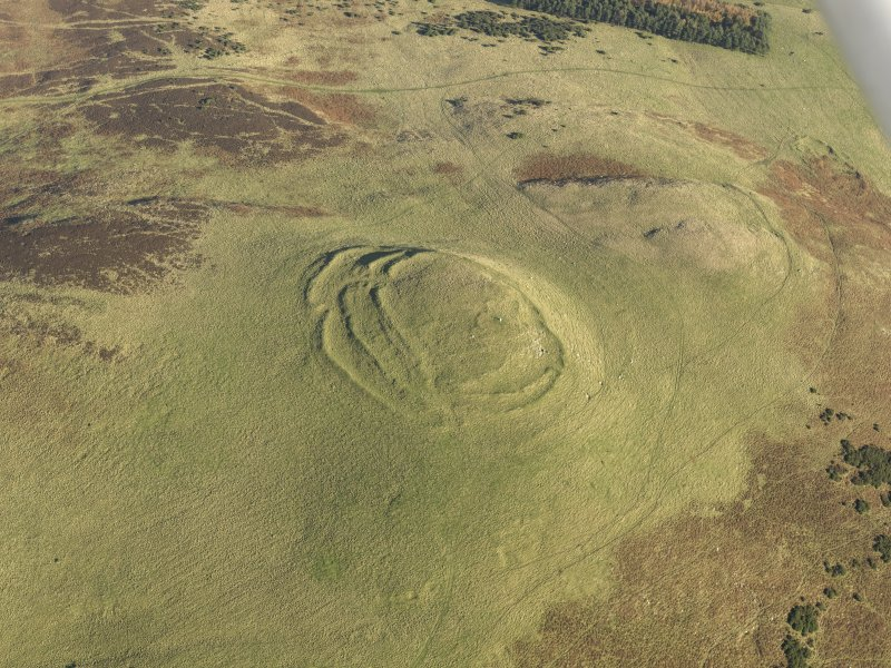 Oblique aerial view of the remains of the fort, cairn and rig at Cockburn Law, taken from the SW.