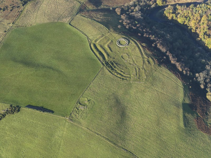 Oblique aerial view of the remains of the fort, settlement and broch at Edin's Hall and the adjacent settlement, taken from the S.