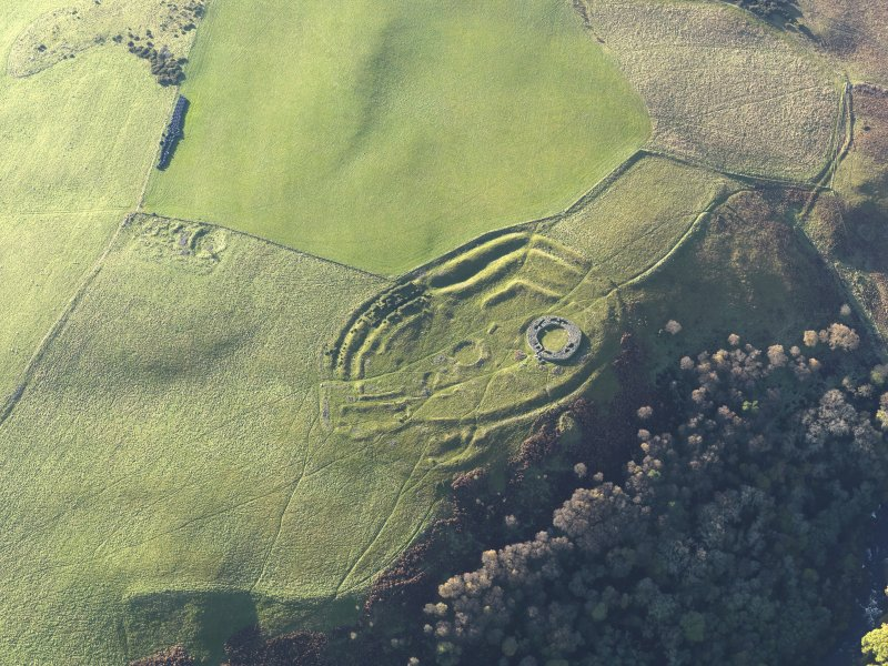 Oblique aerial view of the remains of the fort, settlement and broch at Edin's Hall and the adjacent settlement, taken from the ENE.