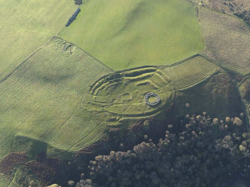 Oblique aerial view of the remains of the fort, settlement and broch at Edin's Hall and the adjacent settlement, taken from the NE.