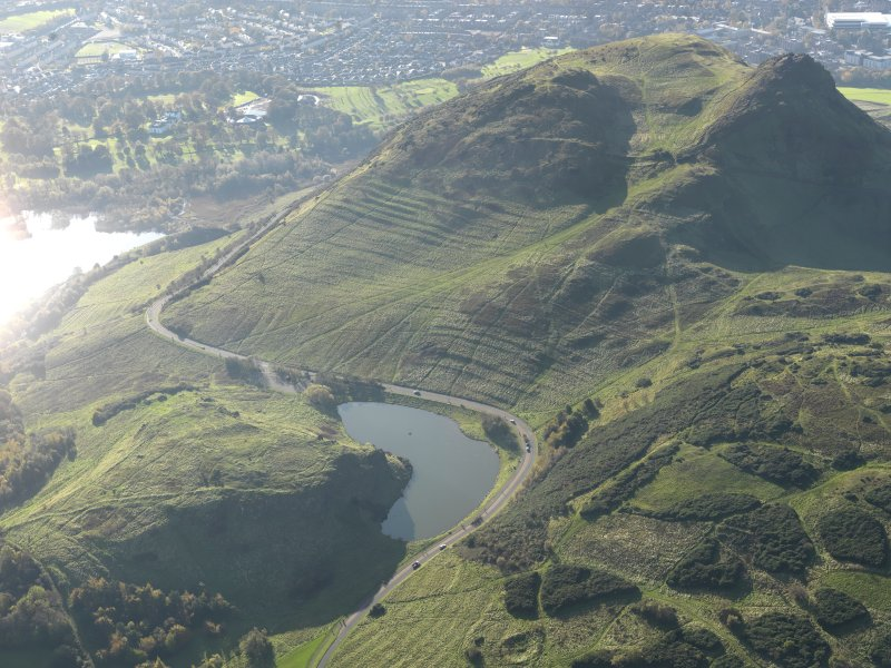 Oblique aerial view of Holyrood Park looking across the remains of the fort and Dunsapie Loch towards Arthur's Seat and the remains of the cultivation terraces and rig, taken from the NE.