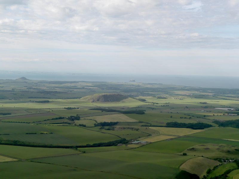 General oblique aerial view with Traprain Law in the middle distance and North Berwick Law beyond, taken from the S.