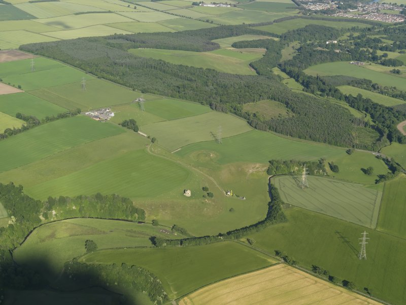 General oblique aerial view of the country house and the remains of the motte and bailey castle, with Hirsel Law beyond, taken from the NW.