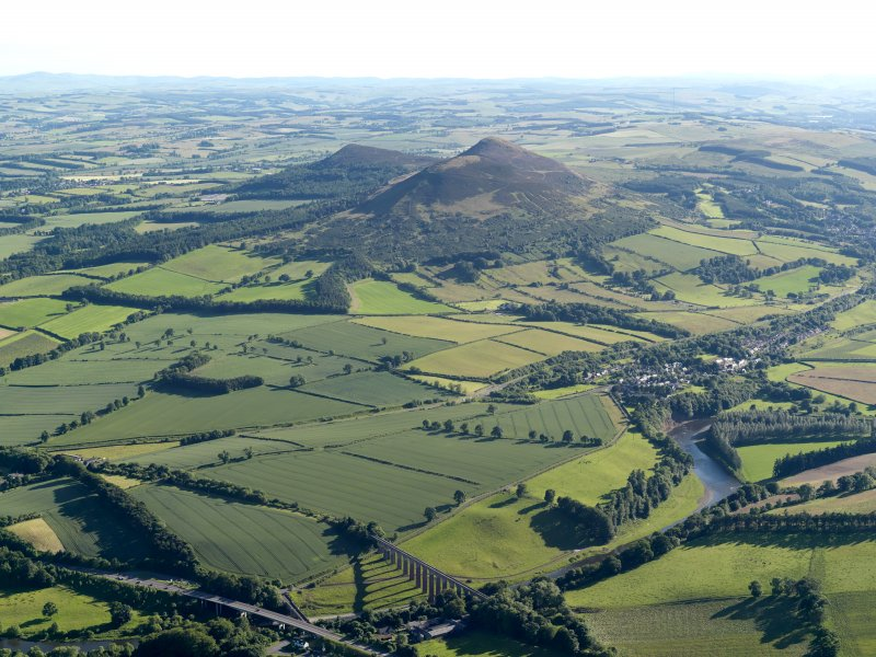General oblique aerial view looking across the bridge, viaduct, village and site of the Roman fort  towards the fort and Eildon Hills, taken from the NE.