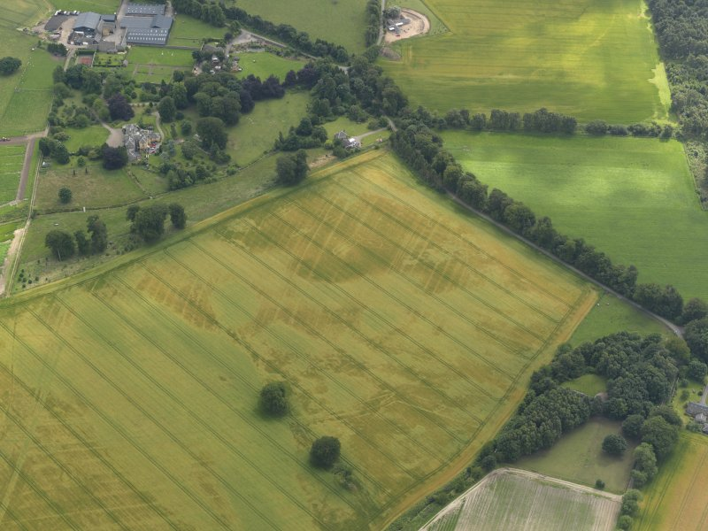 Oblique aerial view of the cropmarks of the buildings and rig and furrow with Lathrisk House adjacent, taken from the N.