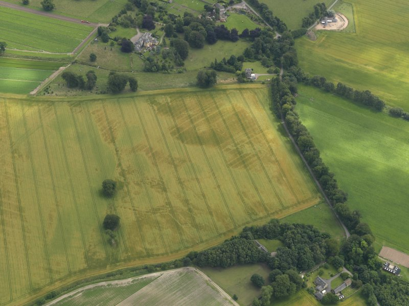 Oblique aerial view of the cropmarks of the buildings and rig and furrow with Lathrisk House adjacent, taken from the NNW.