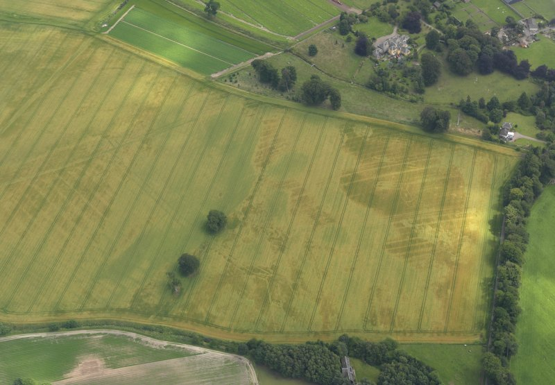 Oblique aerial view of the cropmarks of the buildings and rig and furrow with Lathrisk House adjacent, taken from the NW.
