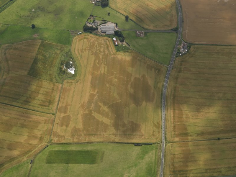 Oblique aerial view of the cropmarks of the barrow, ring ditches and pits at Easter Kinnear with the farmsteading adjacent, taken from the NE.