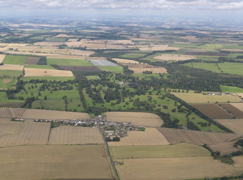 General oblique aerial view centred on Balcarres House and policies with Colinsburgh village adjacent, taken from the S.