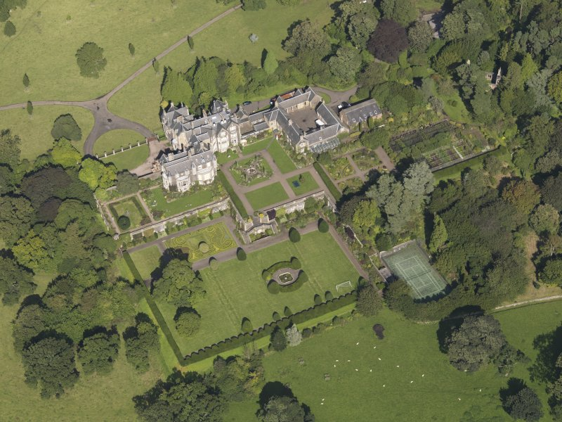 Oblique aerial view centred on the house with the gardens adjacent, taken from the S.
