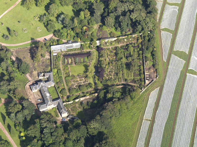 Oblique aerial view centred on the walled garden with the stables adjacent , taken from the S.