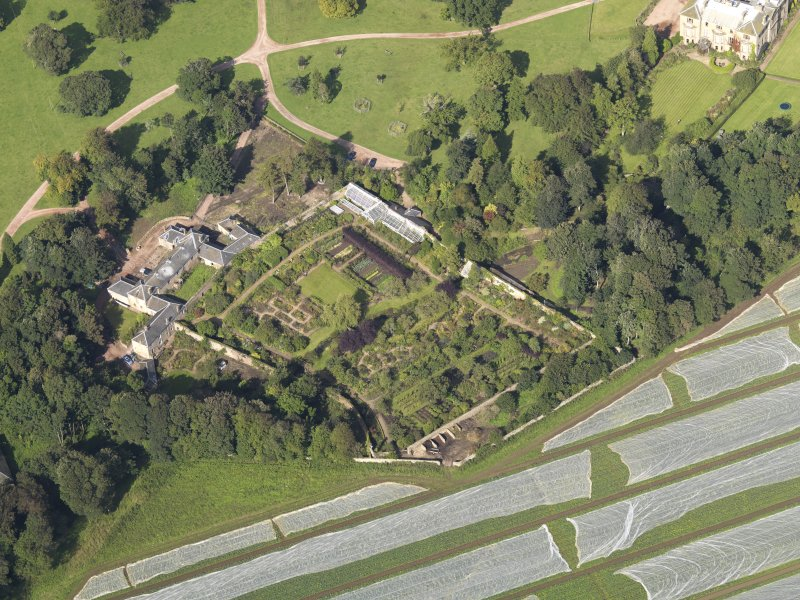 Oblique aerial view centred on the walled garden with the stables adjacent, taken from the SE.