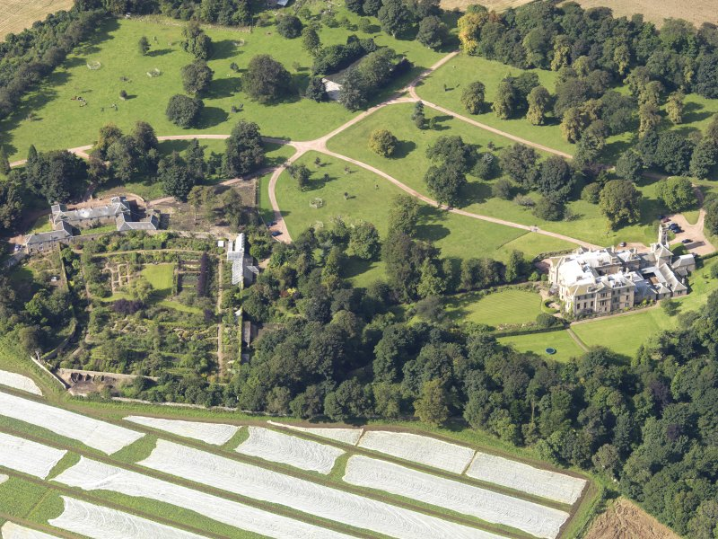 Oblique aerial view centred on the country house with the gardens adjacent , taken from the E.