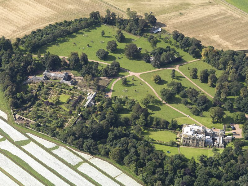 Oblique aerial view centred on the country house with the gardens adjacent , taken from the ENE.