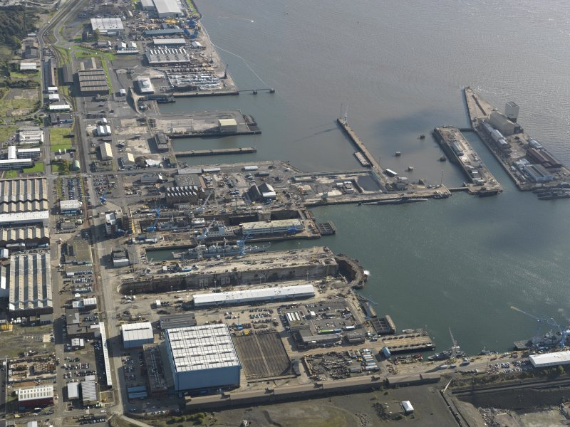 Oblique aerial view centred on the dry docks with the main basin adjacent, taken from the W.