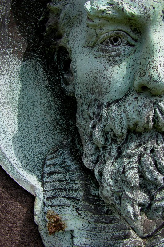 Detail of bronze portrait plaque on monument in memory of George Whitton Johnstone RSA, RSW (died 22nd February 1901).  Located in the upper West section of Morningside Cemetery.