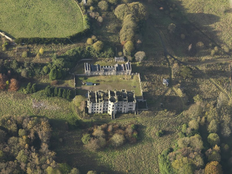 Oblique aerial view centred on the ruins of the country house with the stables adjacent, taken from the SE.