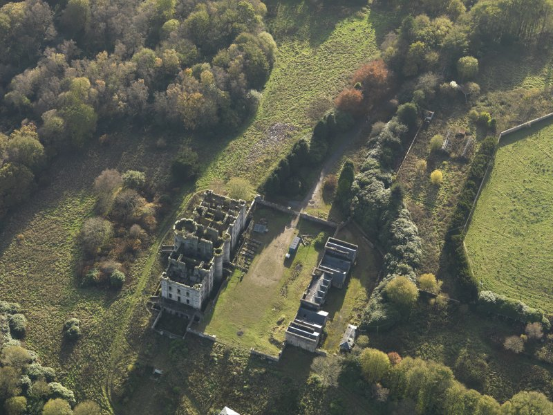 Oblique aerial view centred on the ruins of the country house with the stables adjacent, taken from the NNE.