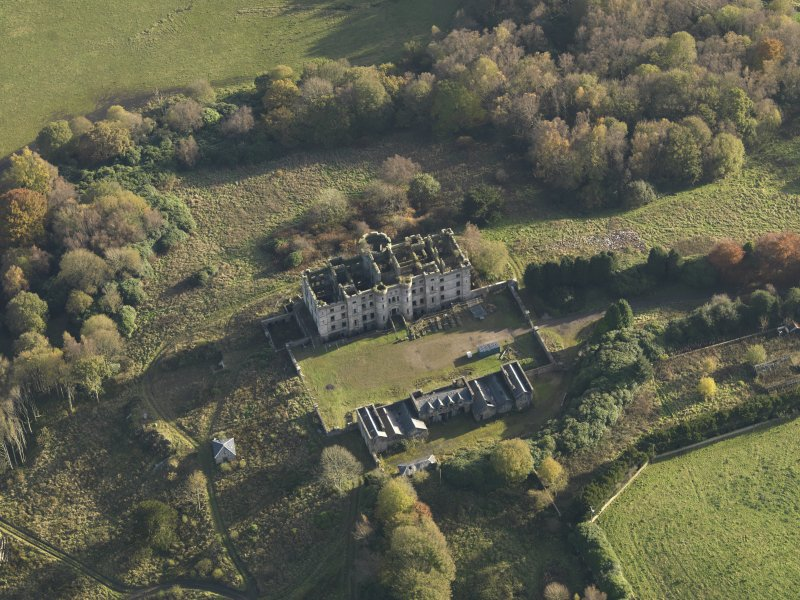 Oblique aerial view centred on the ruins of the country house with the stables adjacent, taken from the N.