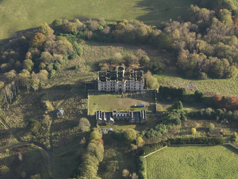 Oblique aerial view centred on the ruins of the country house with the stables adjacent, taken from the NW.