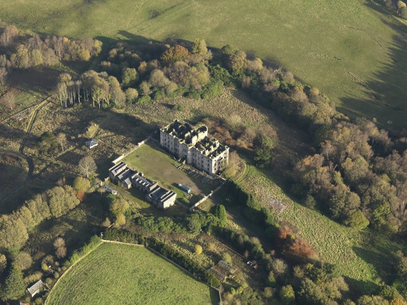 Oblique aerial view centred on the ruins of the country house with the stables adjacent, taken from the W.
