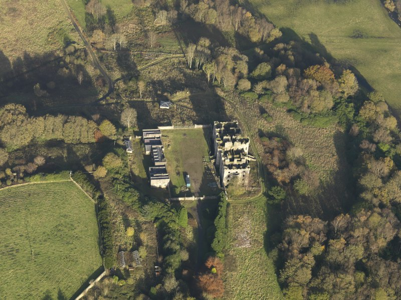 Oblique aerial view centred on the ruins of the country house with the stables adjacent, taken from the SW.