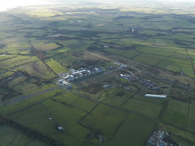 General oblique aerial view centred on the airfield with the Nuclear Power Station adjacent, taken from the SE.