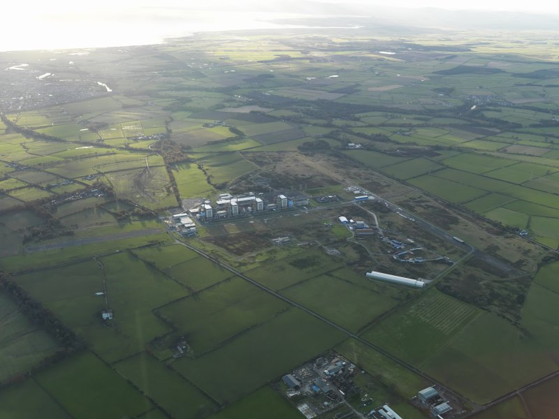 General oblique aerial view centred on the airfield with the Nuclear Power Station adjacent, taken from the E.