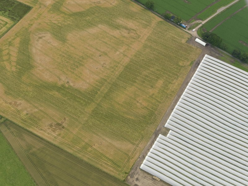 Oblique aerial view centred on the cropmarks of the rig, taken from the N.