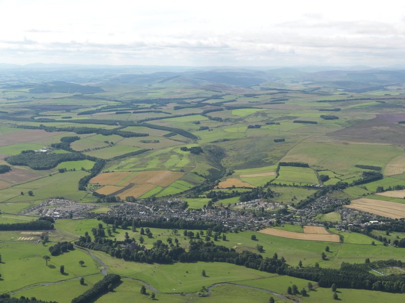 General oblique aerial view centred on the town with the castle and country house in the foreground, taken from the NW.