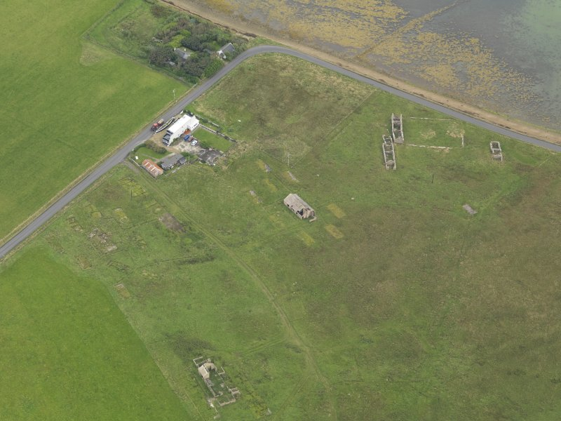 Oblique aerial view centred on the Garrison Theatre with the farmstead adjacent, taken from the NW.