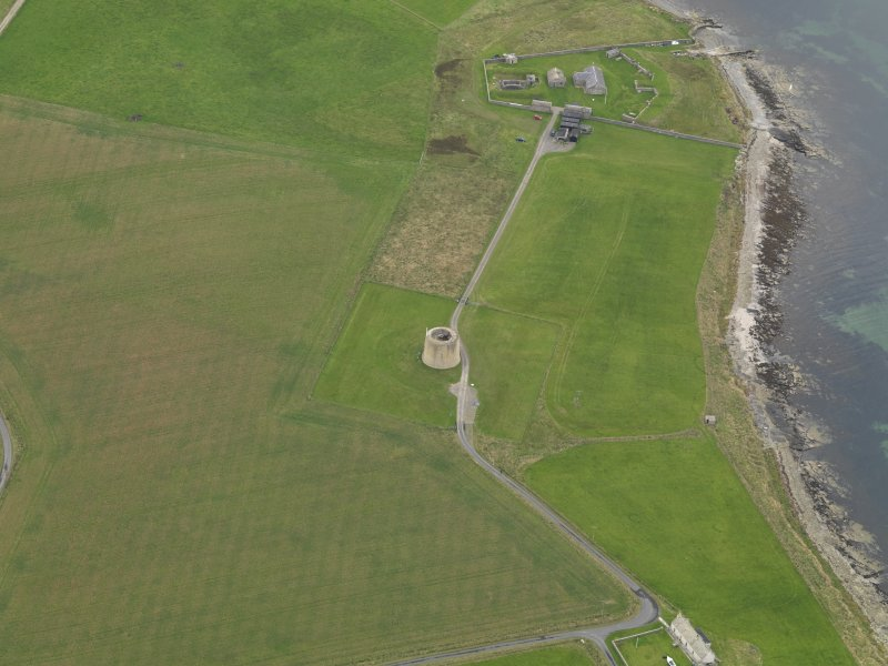 Oblique aerial view centred on the Martello Tower with the early 19th century gun battery adjacent, taken from the SE.