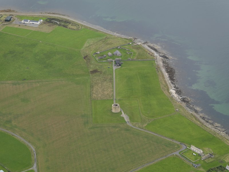 Oblique aerial view centred on the Martello Tower with the early 19th century gun battery adajacent, taken from the SE.