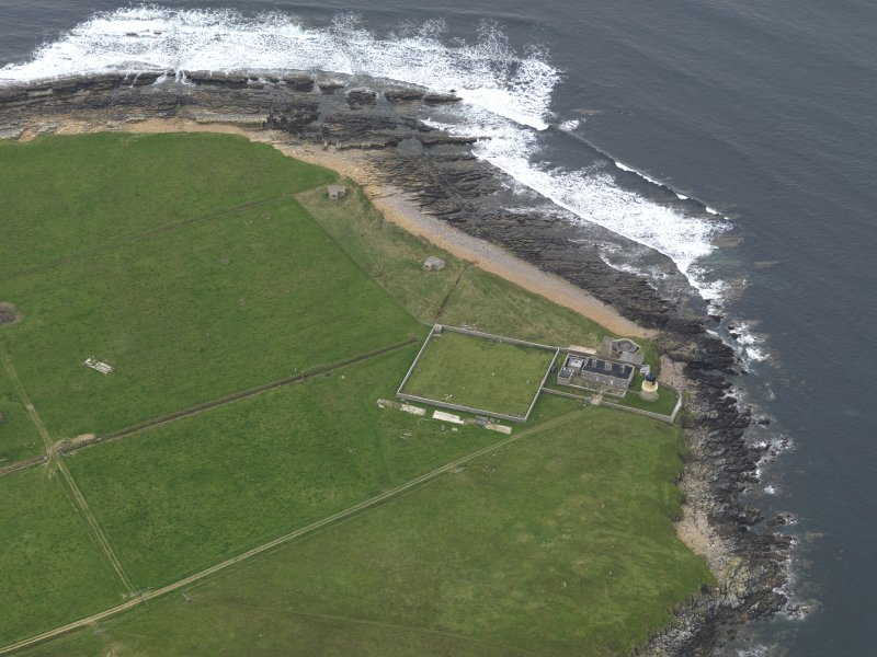 Oblique aerial view centred on the lighthouse with the coastal gun battery adjacent, taken from the SSW.