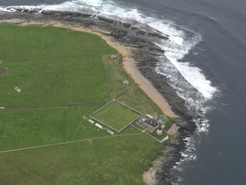 Oblique aerial view centred on the lighthouse with the coastal gun battery adjacent, taken from the SE.