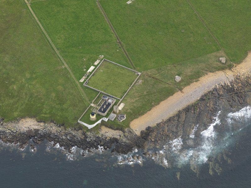 Oblique aerial view centred on the lighthouse with the coastal gun battery adjacent, taken from the N.