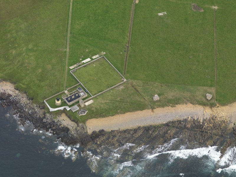 Oblique aerial view centred on the lighthouse with the coastal gun battery adjacent, taken from the NNW.