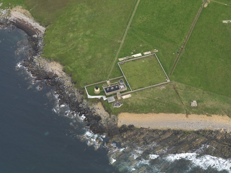 Oblique aerial view centred on Hoy Sound Low lighthouse with the coastal gun battery adjacent, taken from the North West.