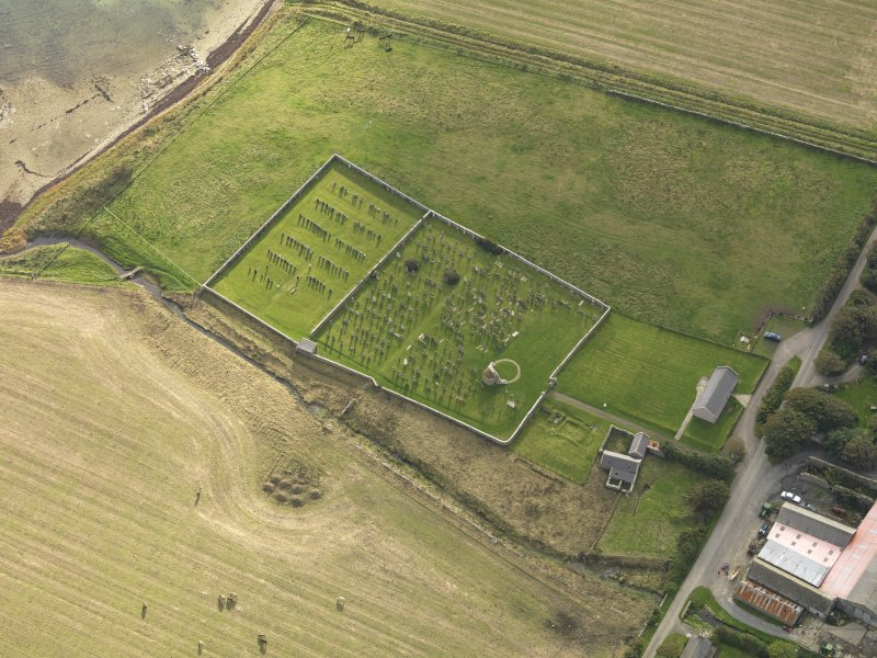 Oblique aerial view centred on the remains of the round church with the burial ground adjacent, taken from the NE.