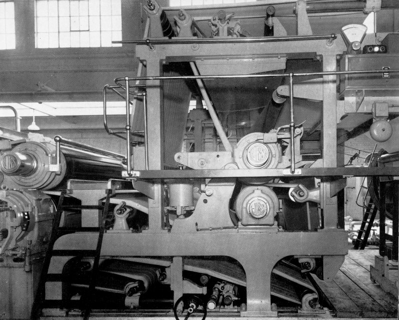 Copy of photograph of paper making machine (no.6), Wet Press Section comprises two presses, the first being the straight through suction type with 'Millspaugh' Suction Roll and the second, a plain reversing press. Both the top granite rollers are carried in roller bearings in spherical housings. The cast-steel levers supporting these rolls are equipped with double acting air cylinders for applying pressure as well as raising clear when changing felts, from the JB&S Machine 161 catalogue, James Bertram and Son Ltd, Leith Walk, Edinburgh, circa 1953. The catalogue describes and illustrates some of the features of the No 161 machine 'recently installed at the well known Mill of Guard Bridge Paper Co Ltd, Fife , Scotland designed with the co-operation of the Mill Staff especially for the economical production of the highest quality papers...'