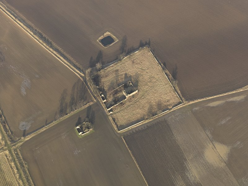 Oblique aerial view centred on the remains of the castle with the remains of the farmstead adjacent, taken from the SSW.