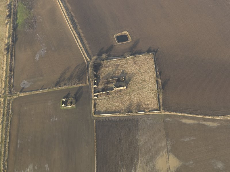 Oblique aerial view centred on the remains of the castle with the remains of the farmstead adjacent, taken from the S.