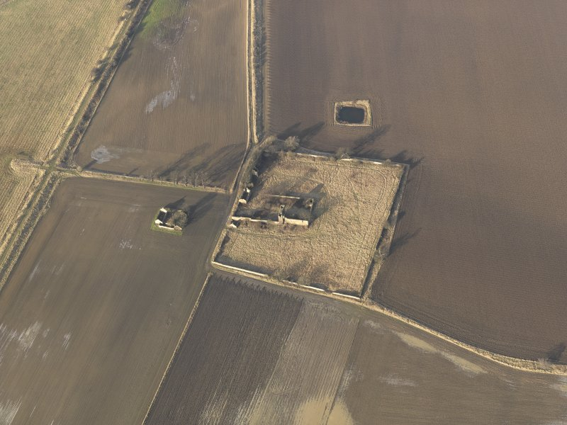 Oblique aerial view centred on the remains of the castle with the remains of the farmstead adjacent, taken from the SSE.