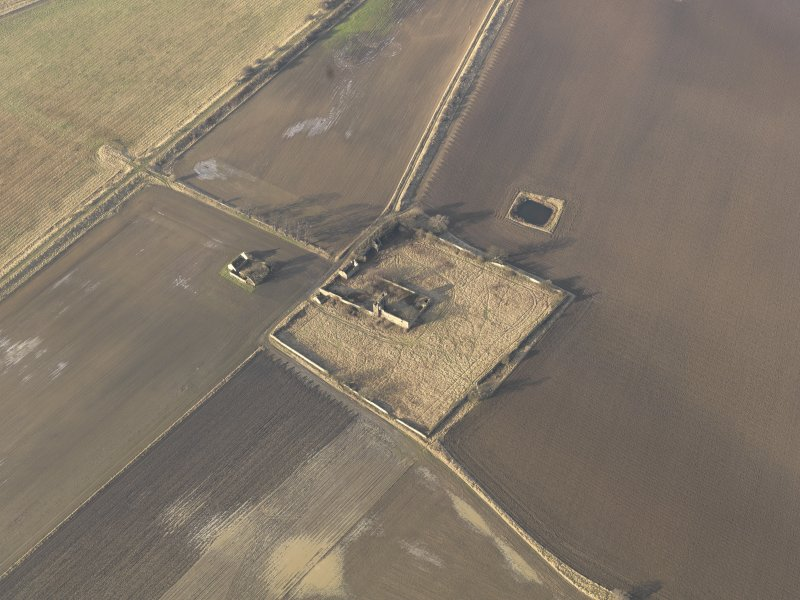 Oblique aerial view centred on the remains of the castle with the remains of the farmstead adjacent, taken from the SE.
