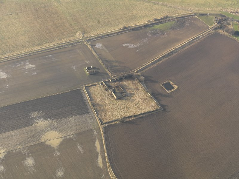 Oblique aerial view centred on the remains of the castle with the remains of the farmstead adjacent, taken from the E.