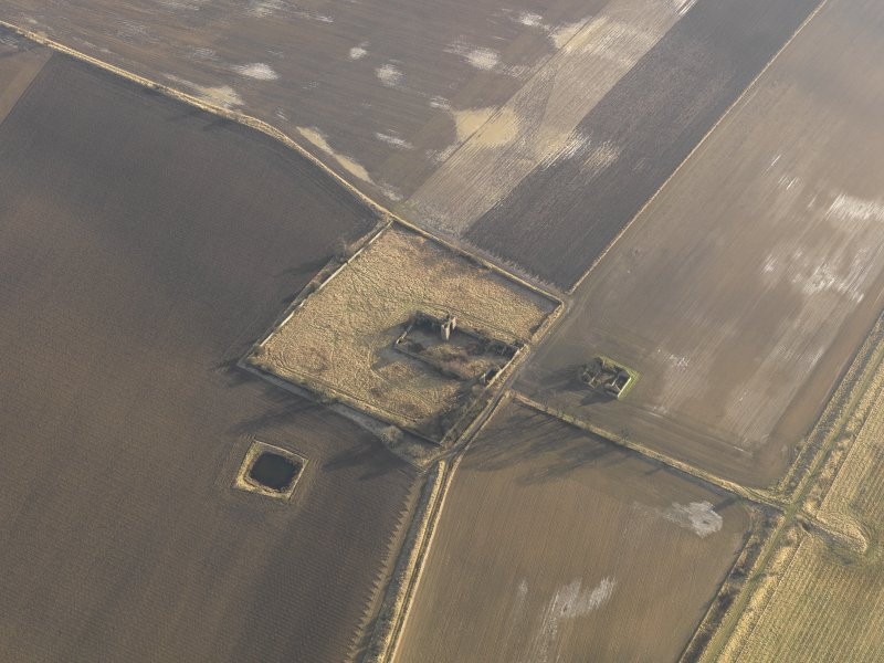 Oblique aerial view centred on the remains of the castle with the remains of the farmstead adjacent, taken from the NW.